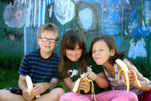 three kids smiling eating banans infront of a art painted wall